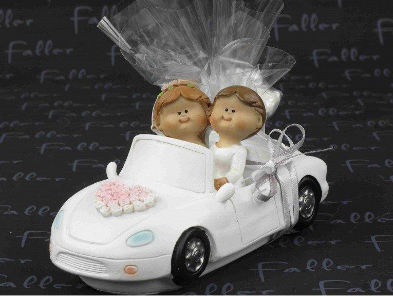 Jeunes mariees dans voiture avec dragees de mariage